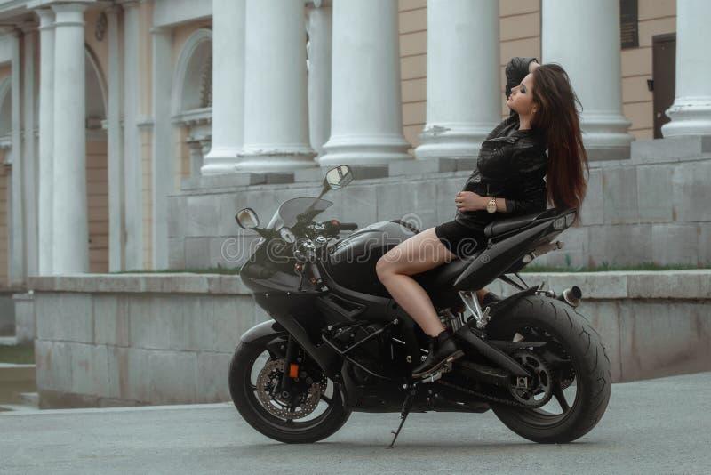 La fille de motard monte une moto sous la pluie Vue de la première personne image stock
