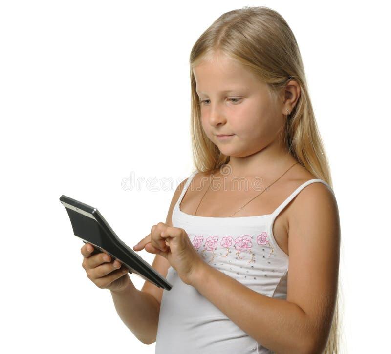 La fille de neuf ans la blonde avec la calculatrice photographie stock