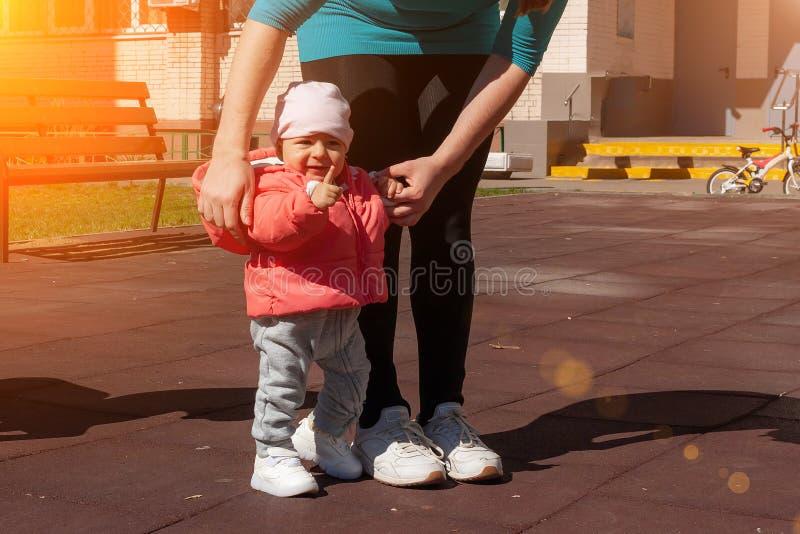 La fille de neuf mois montre son doigt M?re tenant son b?b? dans le rose ? la main et l'enseignant faisant des premi?res ?tapes M images stock