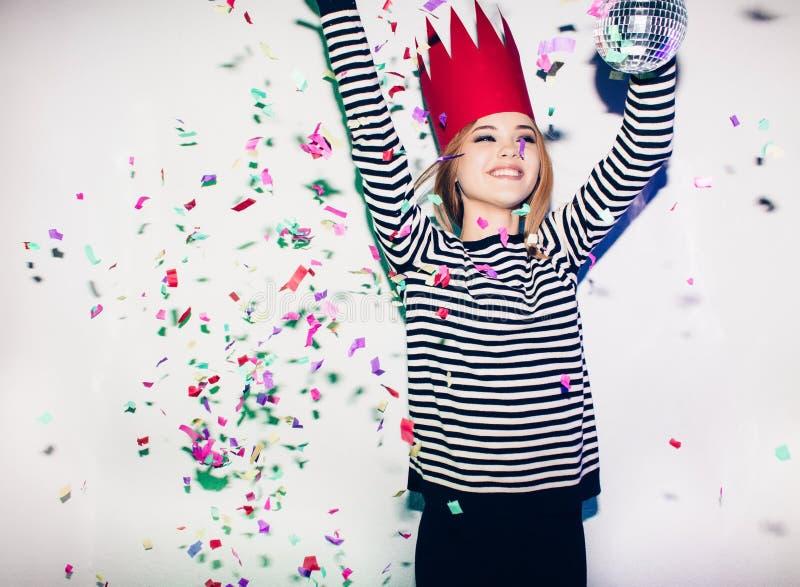 La fille de partie dans les projecteurs colorés et les confettis souriant sur le fond blanc célébrant l'événement brightful, port images stock