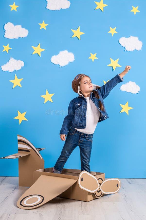 La fille de petit enfant dans un costume pilote du ` s est jouante et rêvante du vol au-dessus des nuages photo libre de droits