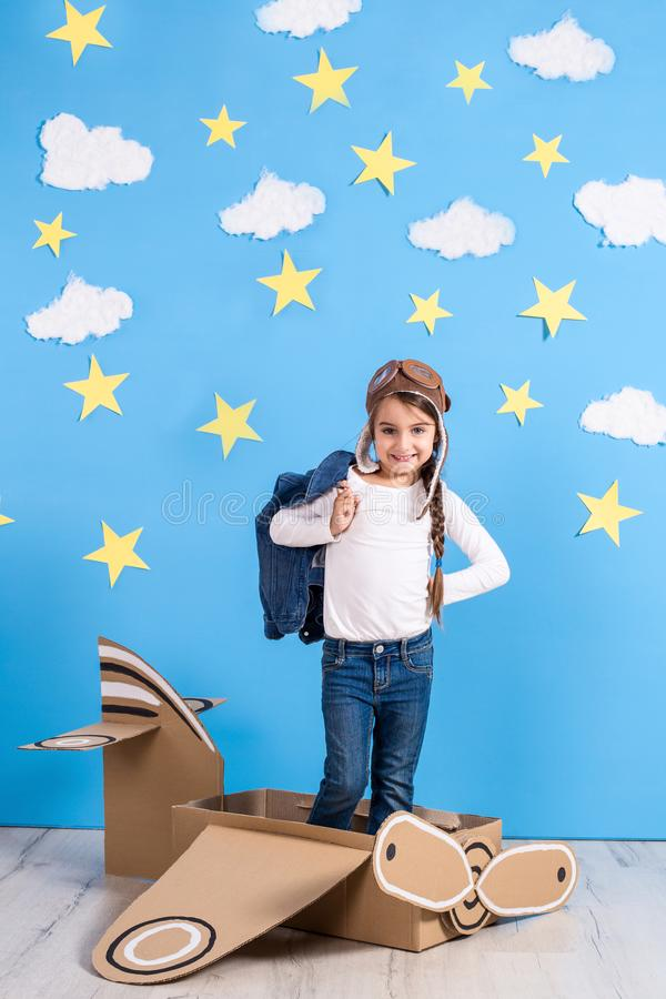 La fille de petit enfant dans un costume pilote du ` s est jouante et rêvante du vol au-dessus des nuages image stock
