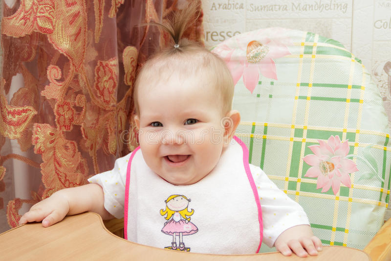 La fille de petit enfant s'assied dans un highchair photo stock