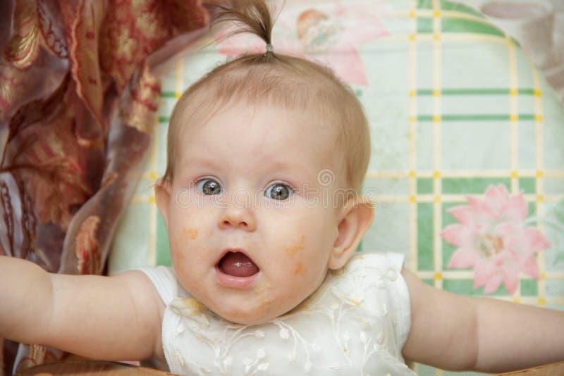 La fille de petit enfant s'assied dans un highchair et mange des biscuits photographie stock libre de droits