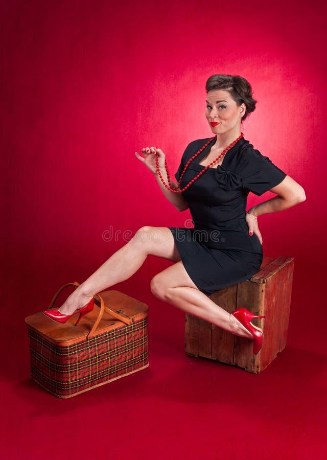 La fille de pin-up dans la robe noire s'assied sur la boîte en bois photos libres de droits