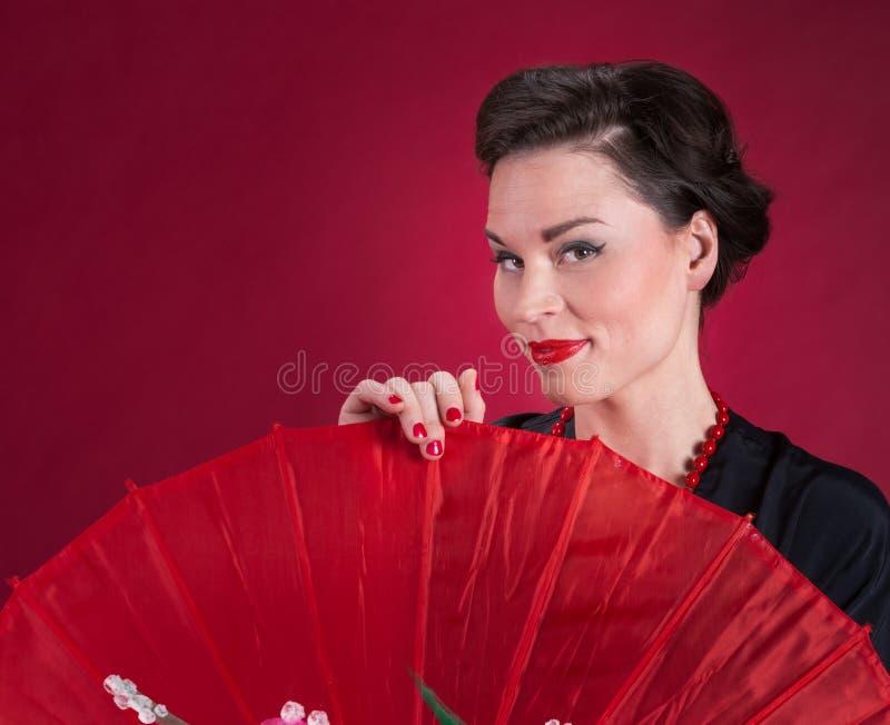 La fille de pin-up regarde au-dessus du parasol rouge photos stock