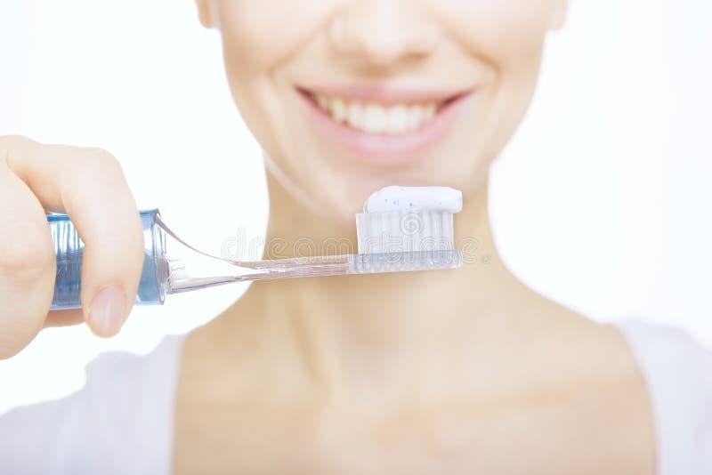 La fille de plan rapproché avec des dents de nettoyage de brosse à dents à la maison, blanchissent l'appel photo stock