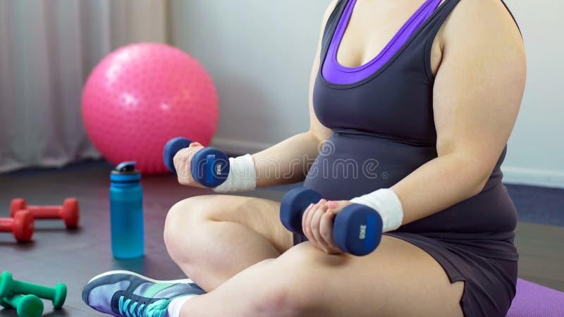 La fille de poids excessif soulevant des haltères pour le bras fort muscles, la séance d'entraînement à la maison, sport photo libre de droits