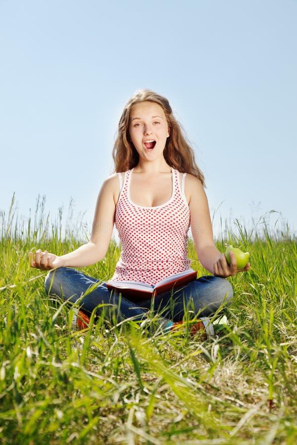 La fille de portrait s'assied sur une herbe photos stock