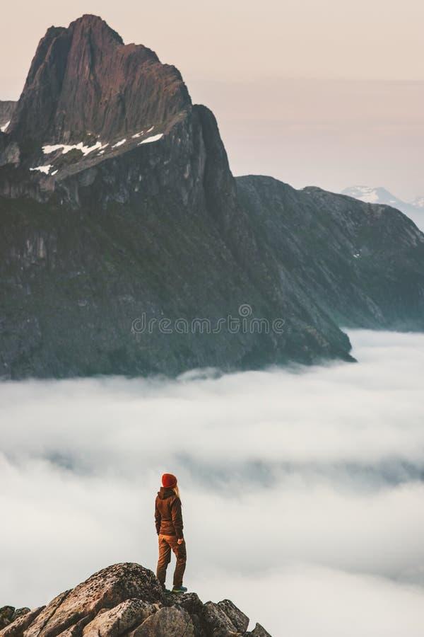 La fille de randonneur sur le bord de falaise au-dessus des nuages voyagent en montagnes photographie stock libre de droits