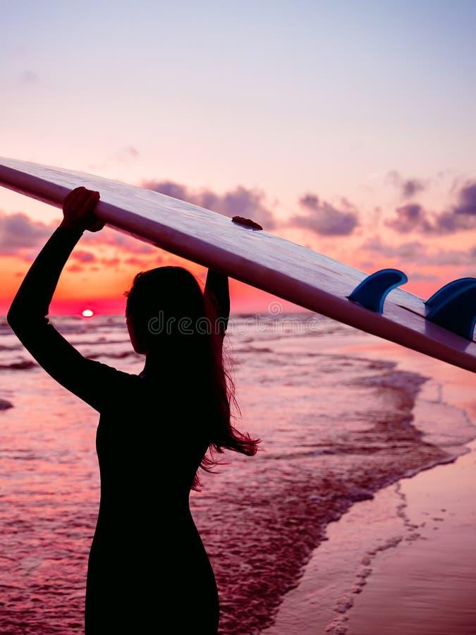 La fille de ressac avec de longs cheveux vont à surfer Silhouette d'une femme avec la planche de surf sur une plage au coucher du image stock