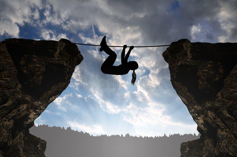 La fille de silhouette s'élève sur une corde au-dessus d'un abîme photographie stock libre de droits