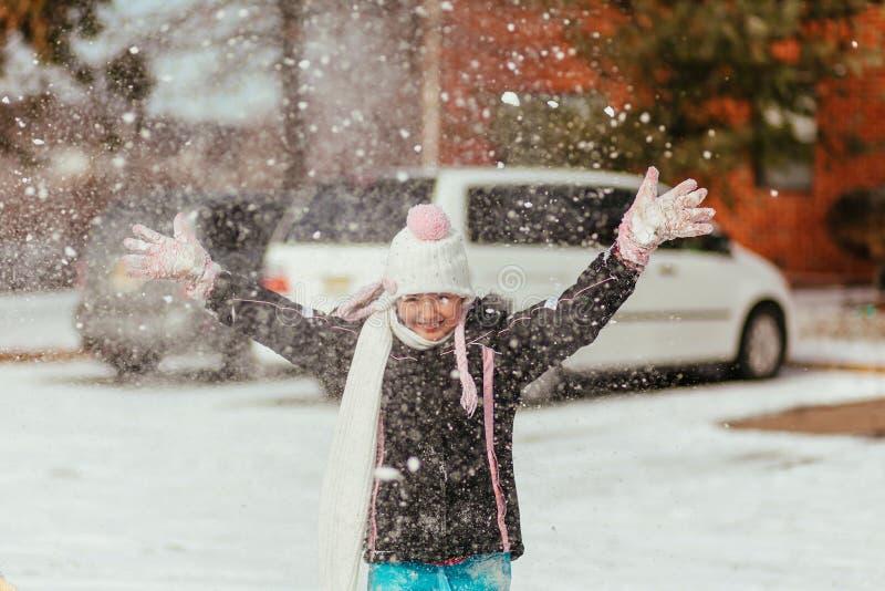 la fille de sourire assez petite avec de longs cheveux blonds dans le rose a tricoté le chapeau et l'écharpe et le manteau beige  photo stock