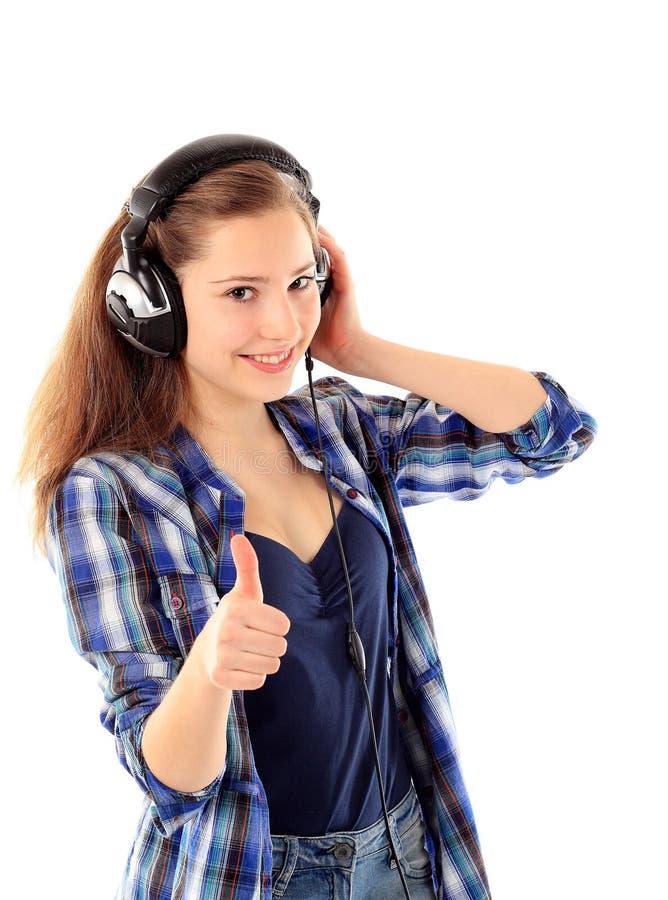 La fille de sourire avec des écouteurs manient maladroitement vers le haut image stock