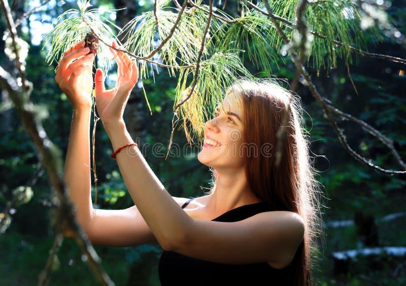 La fille de sourire déchire un morceau d'une branche de cèdre dans le taiga sibérien d'été photos libres de droits