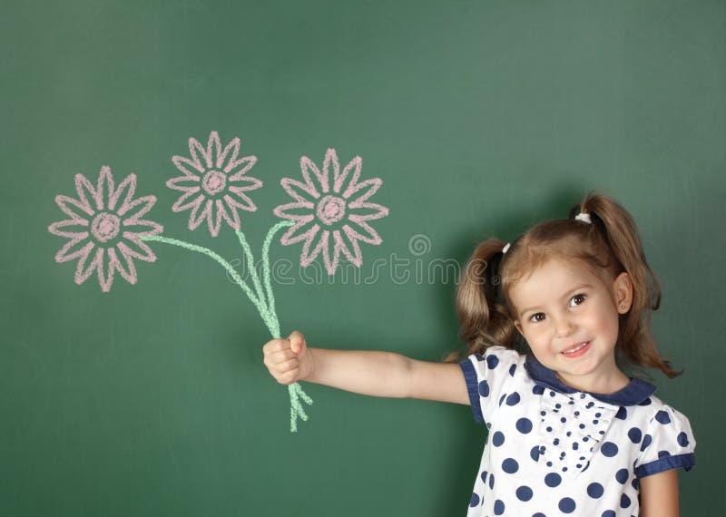 La fille de sourire d'enfant tiennent les fleurs tirées près du tableau noir d'école photos libres de droits