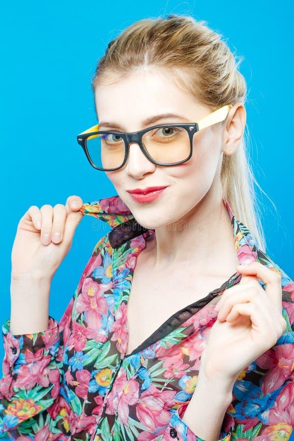 La fille de sourire dans des lunettes pose dans le studio regardant l'appareil-photo Portrait de femme blonde drôle avec la queue images libres de droits