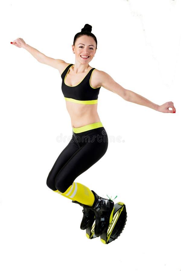 La fille de sourire de brune sautant dans un kangoo saute des chaussures image libre de droits