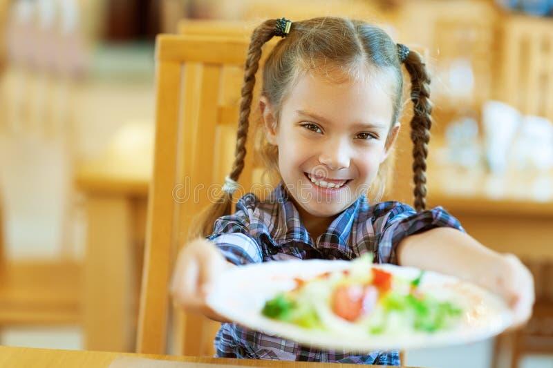 La fille de sourire donne la plaque photographie stock libre de droits