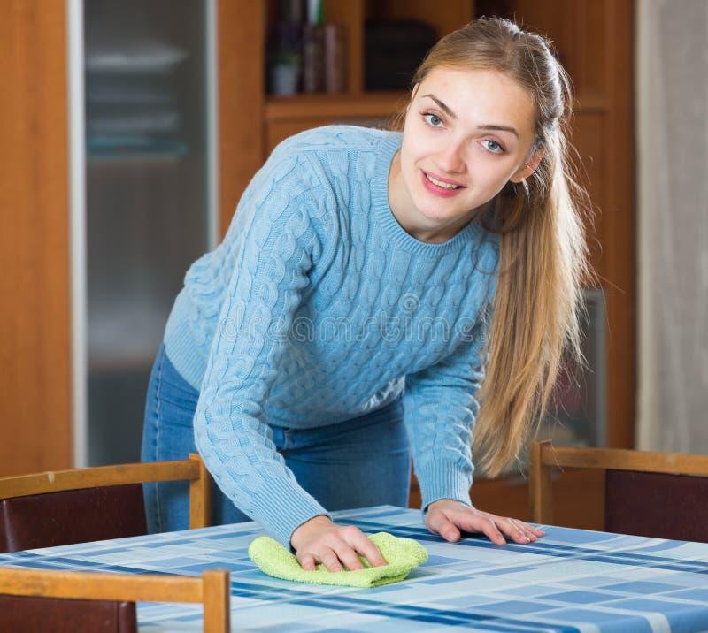 La fille de sourire en saupoudrage bleu de débardeur ajournent à la maison photos libres de droits
