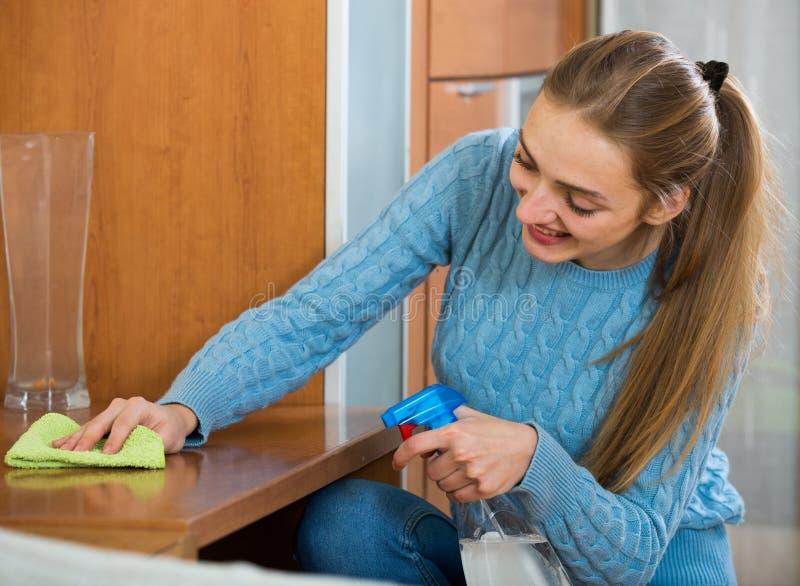 La fille de sourire en saupoudrage bleu de débardeur ajournent à la maison image libre de droits