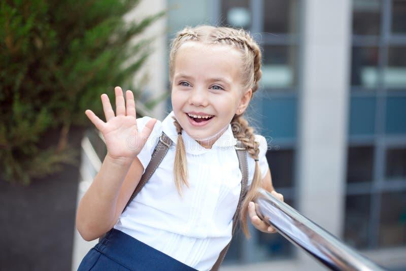 La fille de sourire heureuse va instruire pour la premi?re fois avec le sac vont ? l'?cole primaire photo libre de droits