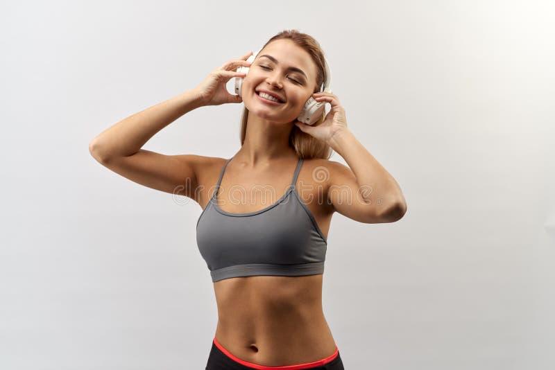 La fille de sourire joyeuse dans le dessus gris de sport avec des écouteurs sur sa tête pose pour un portrait de studio sur le fo images stock
