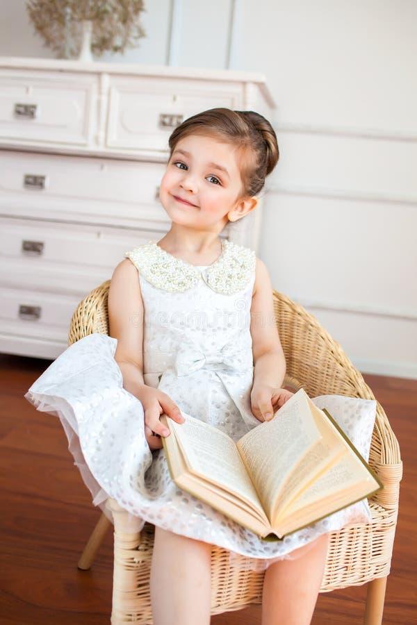 La fille de sourire lisant un livre sur le fauteuil images stock