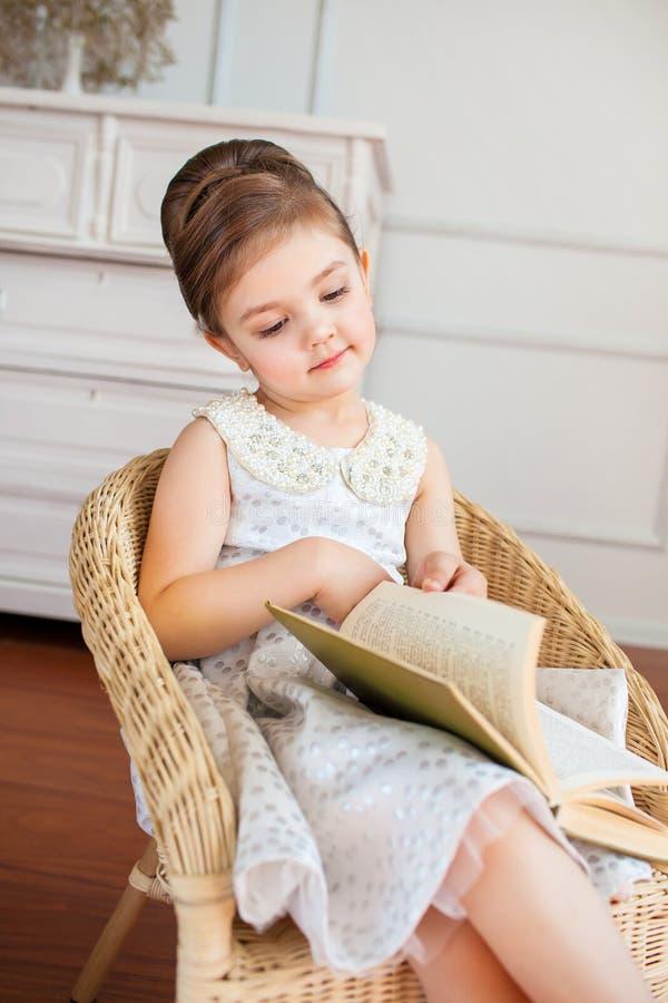 La fille de sourire lisant un livre sur le fauteuil photo stock