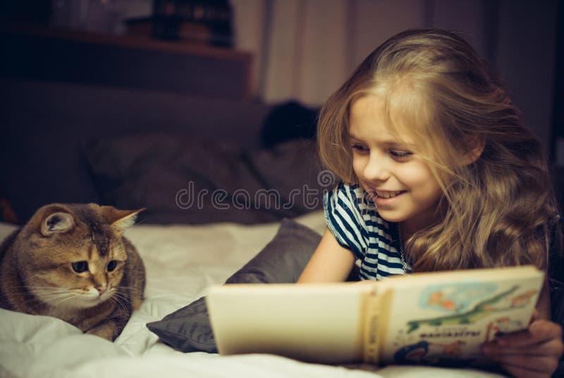 La fille de sourire lit le livre à un chat images libres de droits
