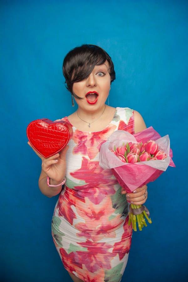 La fille de sourire mignonne dans une robe de ressort tient le bouquet frais rose des fleurs de tulipe sur un fond bleu dans le s photo libre de droits