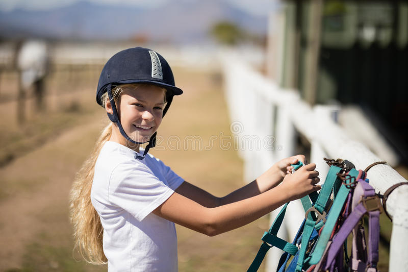 La fille de sourire prenant un cheval musellent dans le ranch images stock