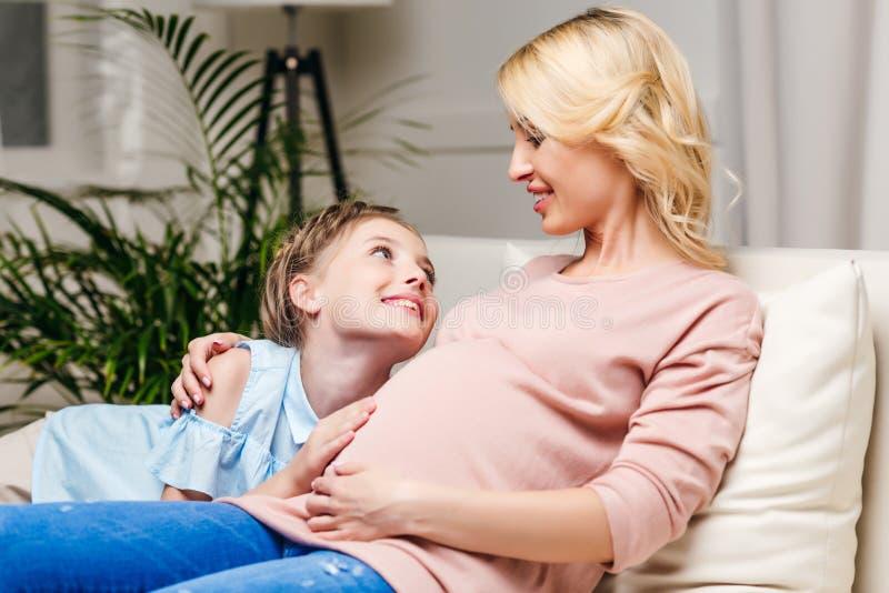 La fille de sourire touchant les mères enceintes se gonflent tout en se reposant sur le sofa image stock