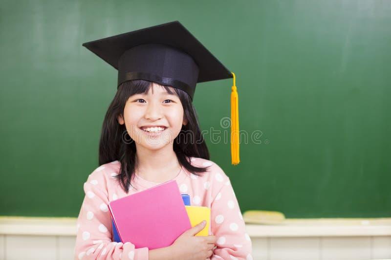 La fille de sourire utilisent un chapeau d'obtention du diplôme image libre de droits