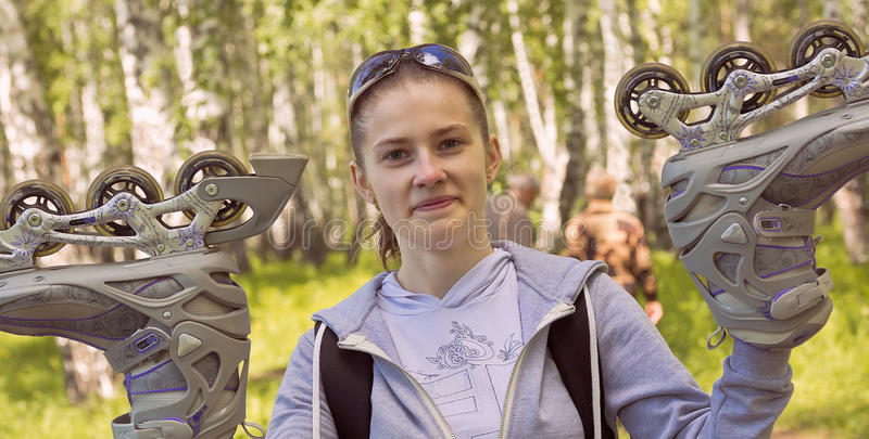 La fille de sports avec des lunettes de soleil soulève des patins de rouleau  images libres de droits