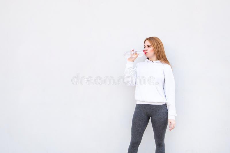 La fille de sports dans l'habillement léger boit des bouteilles de l'eau sur le fond d'un mur blanc et regarde en longueur sur le photos libres de droits