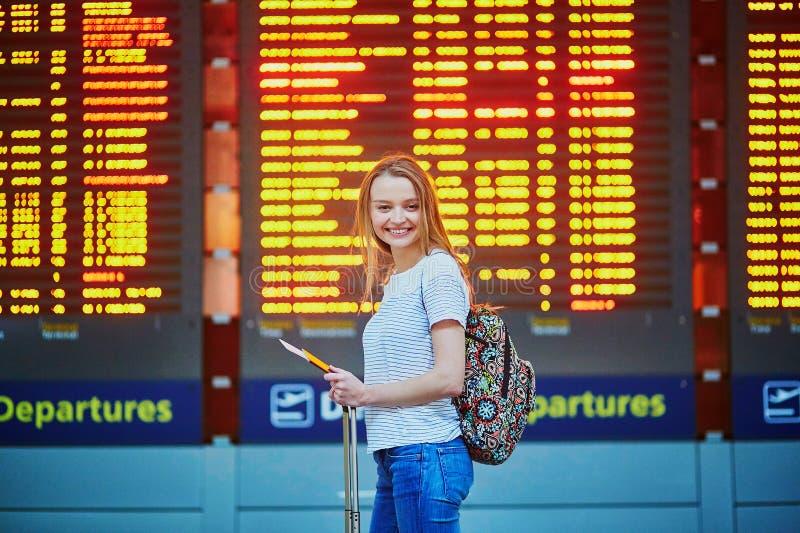 La fille de touristes avec le sac à dos et continuent le bagage dans l'aéroport international, près du conseil de l'information d photo stock
