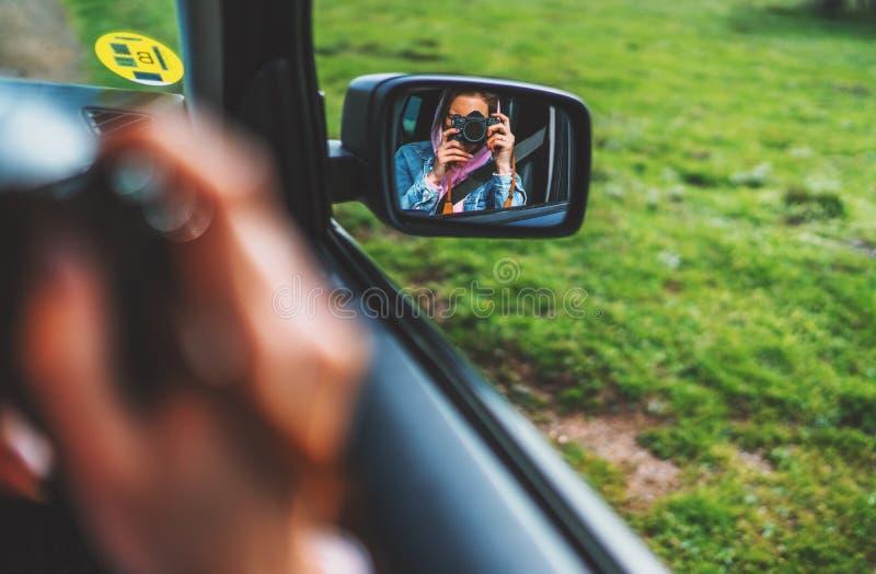 La fille de touristes dans une fenêtre ouverte d'une voiture prenant la photographie cliquent sur sur la rétro caméra de photo de photos stock