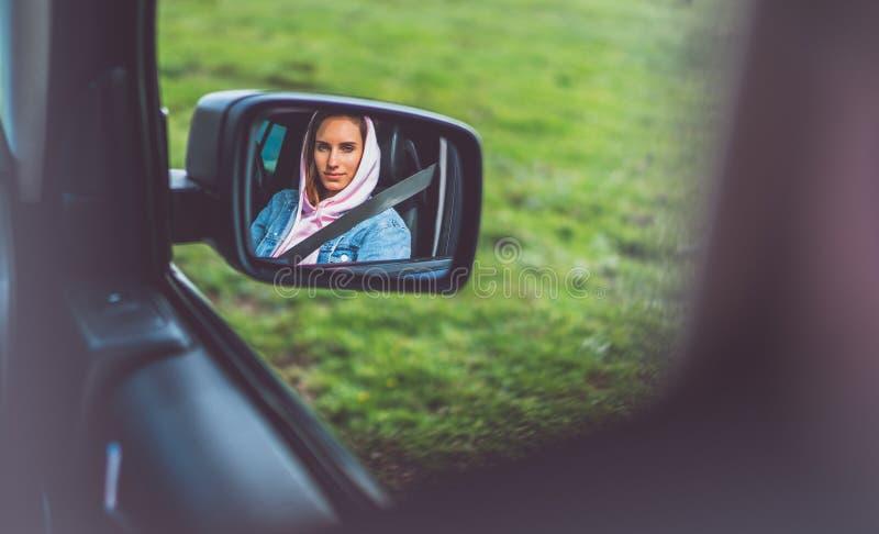 La fille de touristes dans une fenêtre ouverte d'une voiture regardant à la réflexion dans une automobile de miroir, blogger empl photographie stock