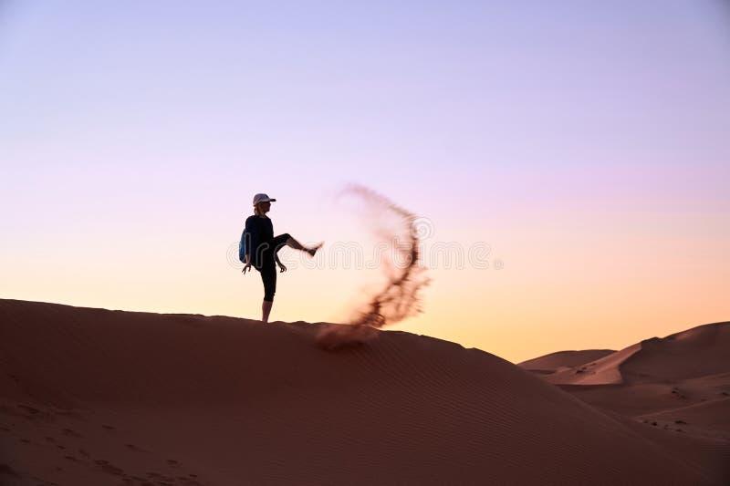 La fille de touristes donne un coup de pied le sable dans le ciel dans le désert du Sahara images libres de droits
