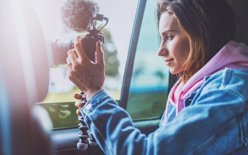 La fille de touristes de sourire dans une fenêtre ouverte d'une voiture automatique prenant la photographie cliquent sur sur la c images stock