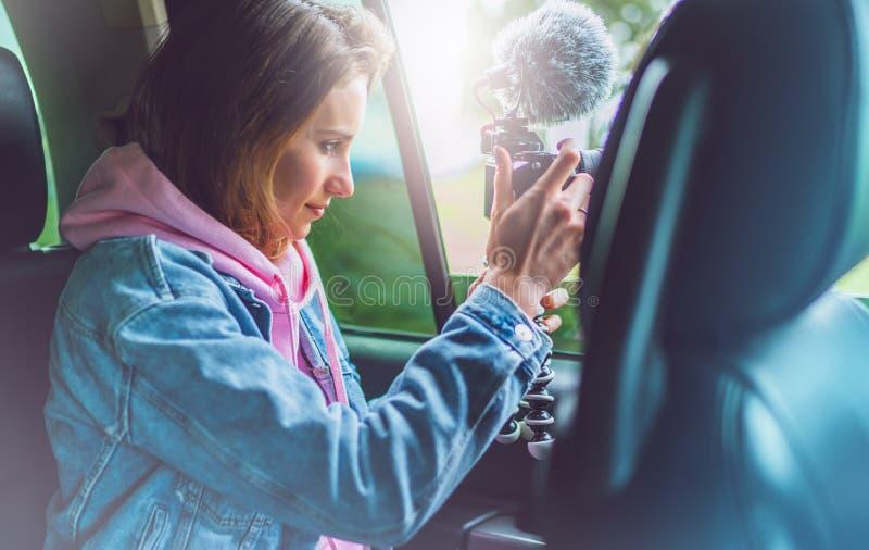 La fille de touristes de sourire dans une fenêtre ouverte d'une voiture automatique prenant la photographie cliquent sur sur la c image libre de droits