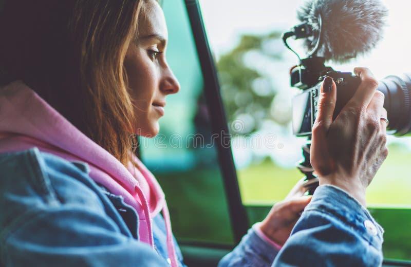 La fille de touristes de sourire dans une fenêtre ouverte d'une voiture automatique prenant la photographie cliquent sur sur la c photos libres de droits
