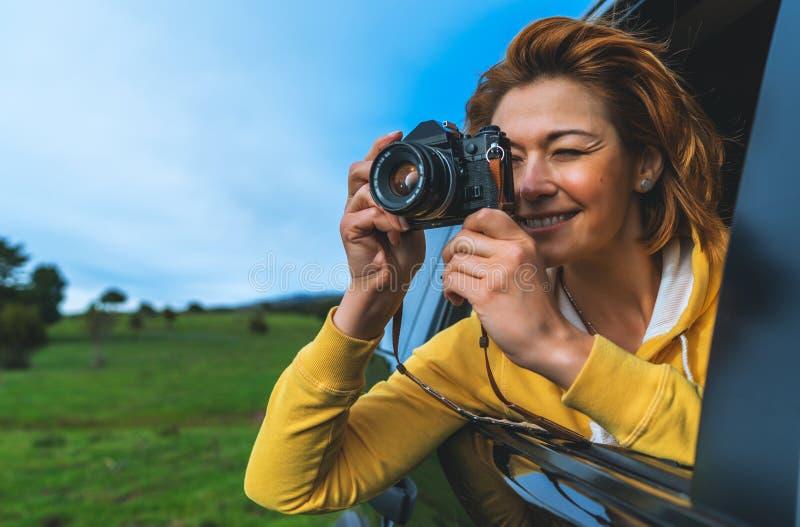 La fille de touristes de sourire dans une fenêtre ouverte d'une voiture automatique prenant la photographie cliquent sur sur la r images libres de droits