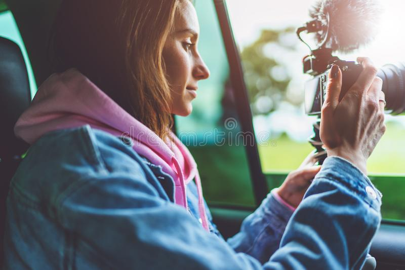 La fille de touristes de sourire dans une fen?tre ouverte d'une voiture automatique prenant la photographie cliquent sur sur la c photo libre de droits