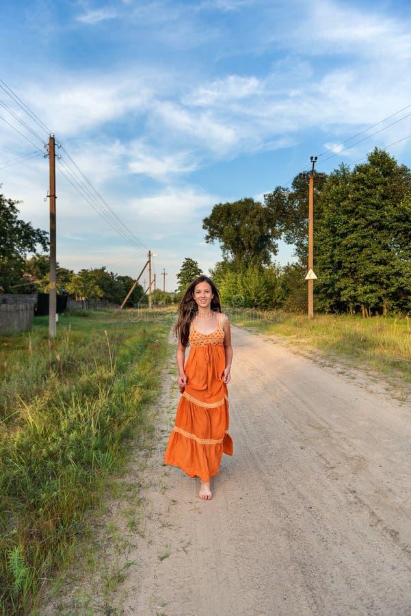 La fille de village court gaiement heureusement nu-pieds le long de la route arénacée dans la campagne image stock
