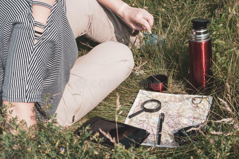 La fille de voyageur dans un T-shirt rayé et un pantalon brun s'assied sur l'herbe photos libres de droits