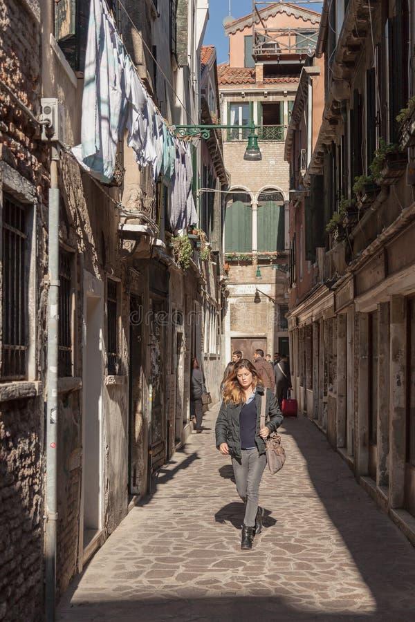 La fille descend une allée ensoleillée à Venise image stock