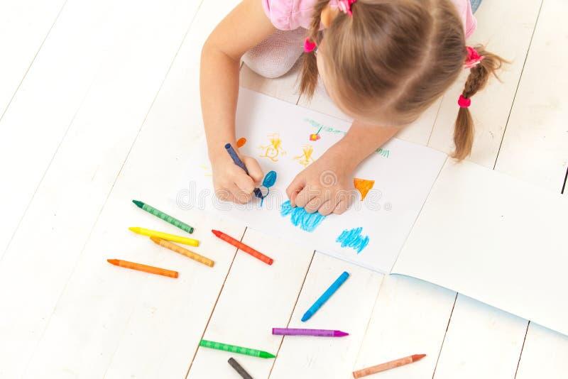 La fille dessine avec des crayons dans l'album photos stock