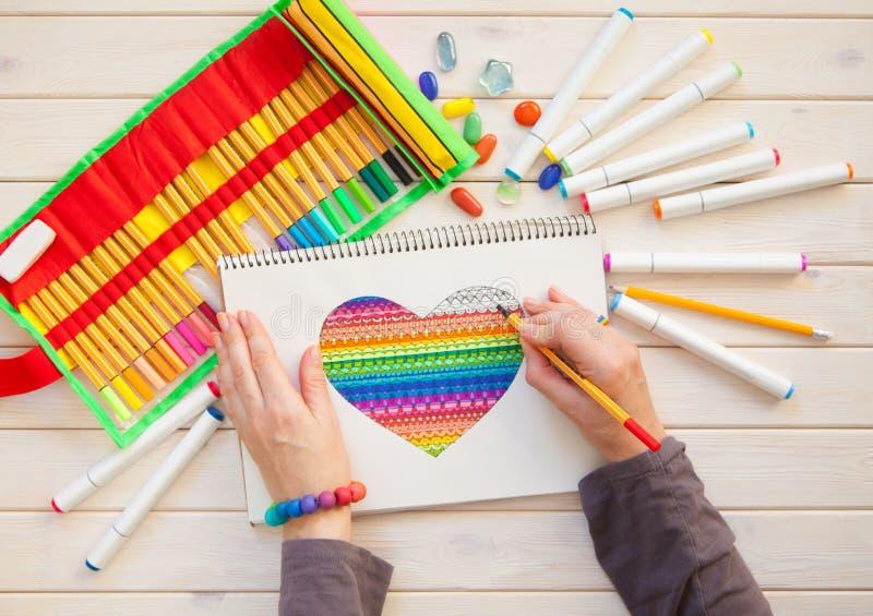La fille dessine la carte postale de marqueurs avec un coeur de couleur Beaucoup marque lumineuse image libre de droits